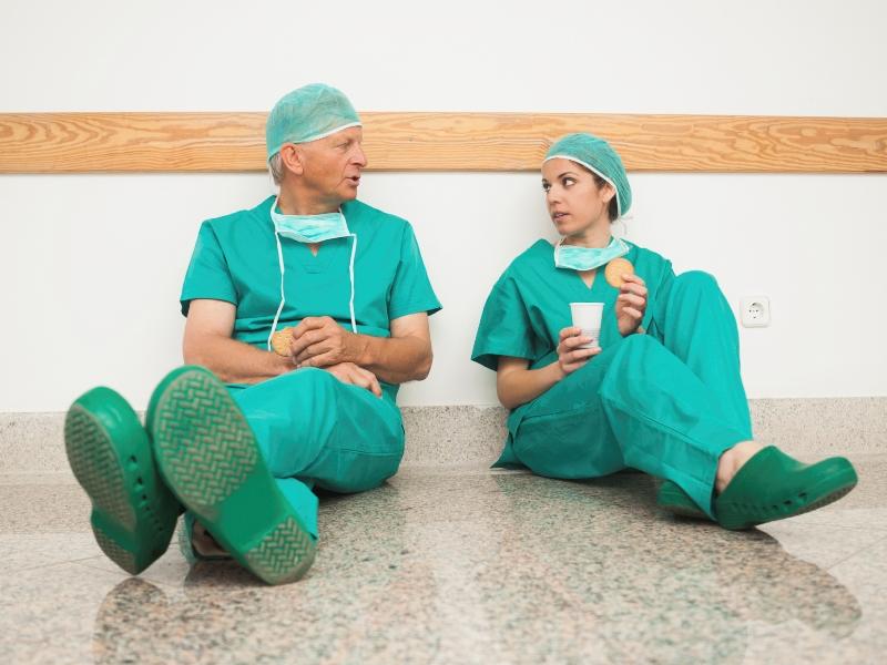 Surgeons sitting against wall