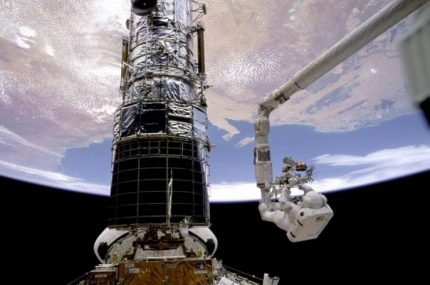 Former NASA astronaut Story Musgrave anchored to a robotic arm during one of his many space walks to make repairs and upgrades to the Hubble Space Telescope. (Photo credit: NASA)